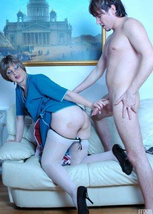 Зрелая бабка пристает к молодому мужу хозяйки, она снимает с него трусы и сосет его хер - фото 14