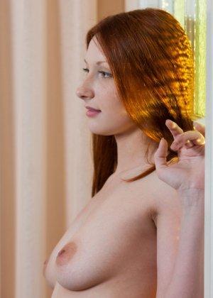 Рыжеволосая девушка принимает разные позы, чтобы показать себя с самых выгодных ракурсов - фото 3