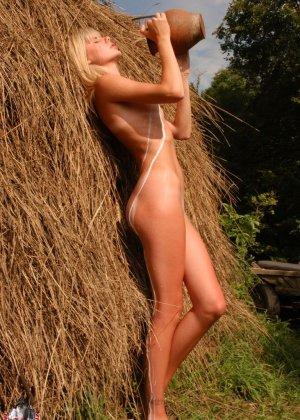 Худенькая блондинка оказывается на сеновале и поливает свое обнаженное тело молоком из кувшина - фото 15