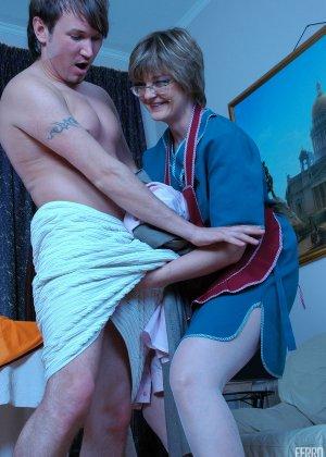 Зрелая бабка пристает к молодому мужу хозяйки, она снимает с него трусы и сосет его хер - фото 5