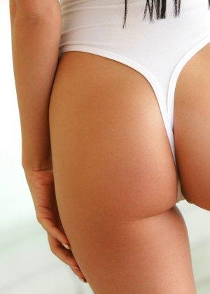 Брюнетка с гладко выбритой пиздой обливает свое тело маслом - фото 4