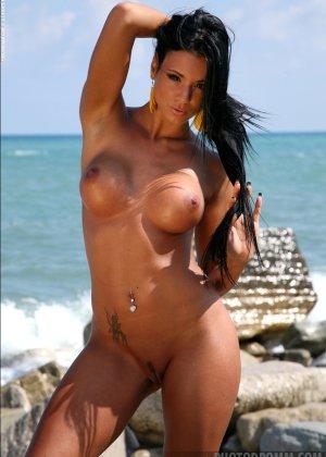 Сексуальная модель со стажем снимает свой влажный купальник на пляже - фото 1