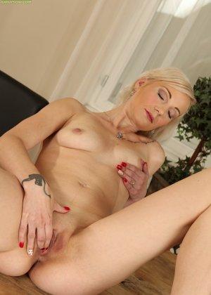 Немолодая блондинка лежит на столе и пальчиками трогает вагинальную дырочку - фото 19