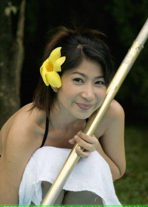 Азиатка с маленькой грудью медленно снимает с себя черный лифчик - фото 1