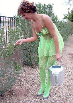 Зрелая кукла показывает свои достоинства когда поливает цветы в саду - фото 2