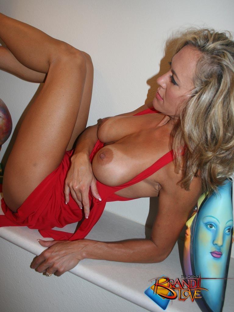 Зрелая блондинка с большими сиськами показывает пизду из под красного платья