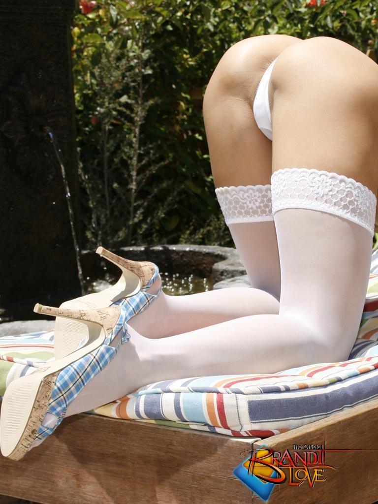 Голая женщина блондинка лежит в белых чулках на шезлонге