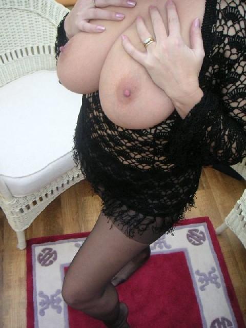 Зрелая дама с большой натуральной грудью откровенно сидит на кресле