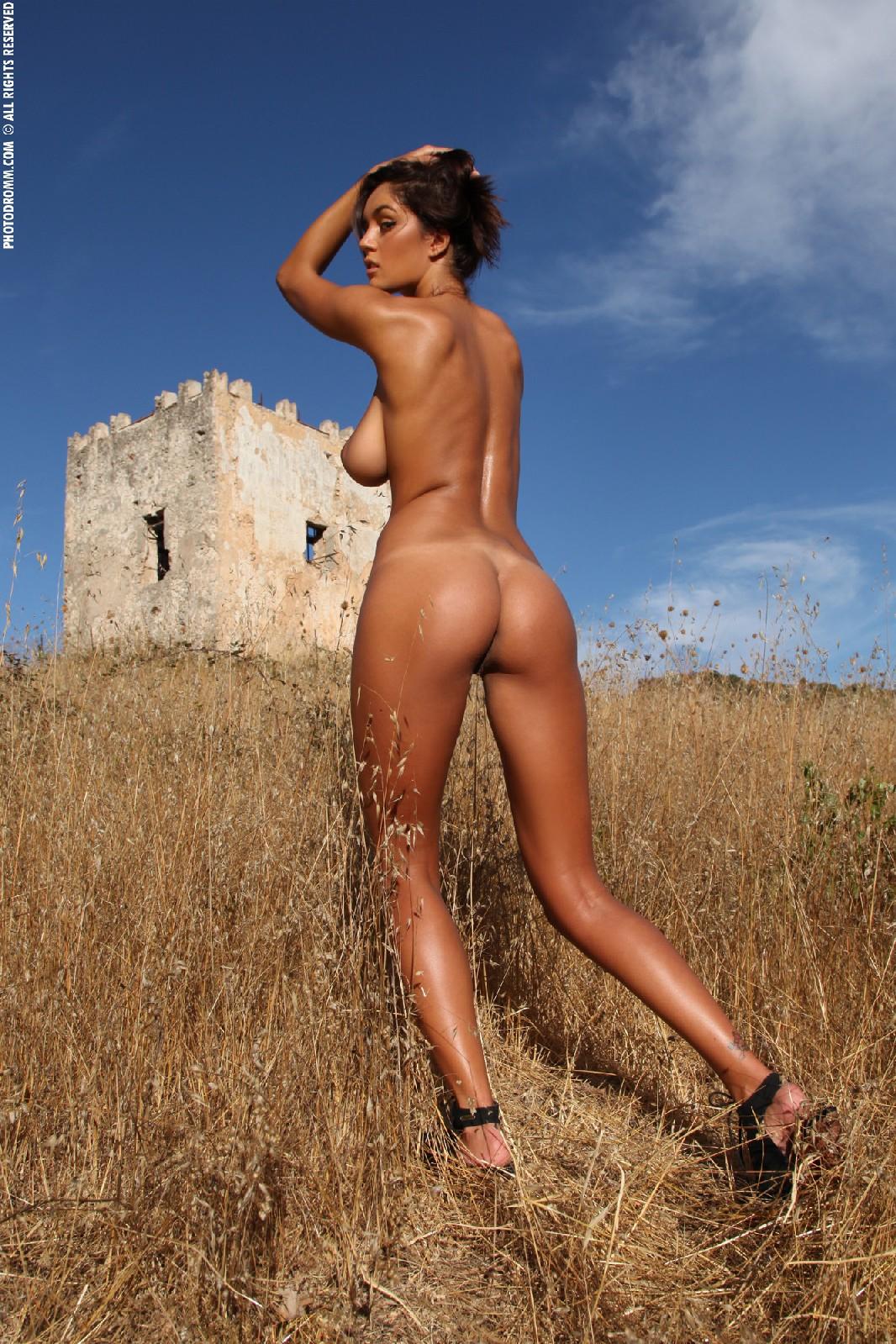 Девушка с большими сиськами фотографируется в поле
