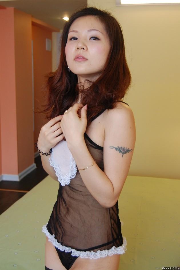 Милая азиатка лежит в кровати в эротическом нижнем белье и чулках