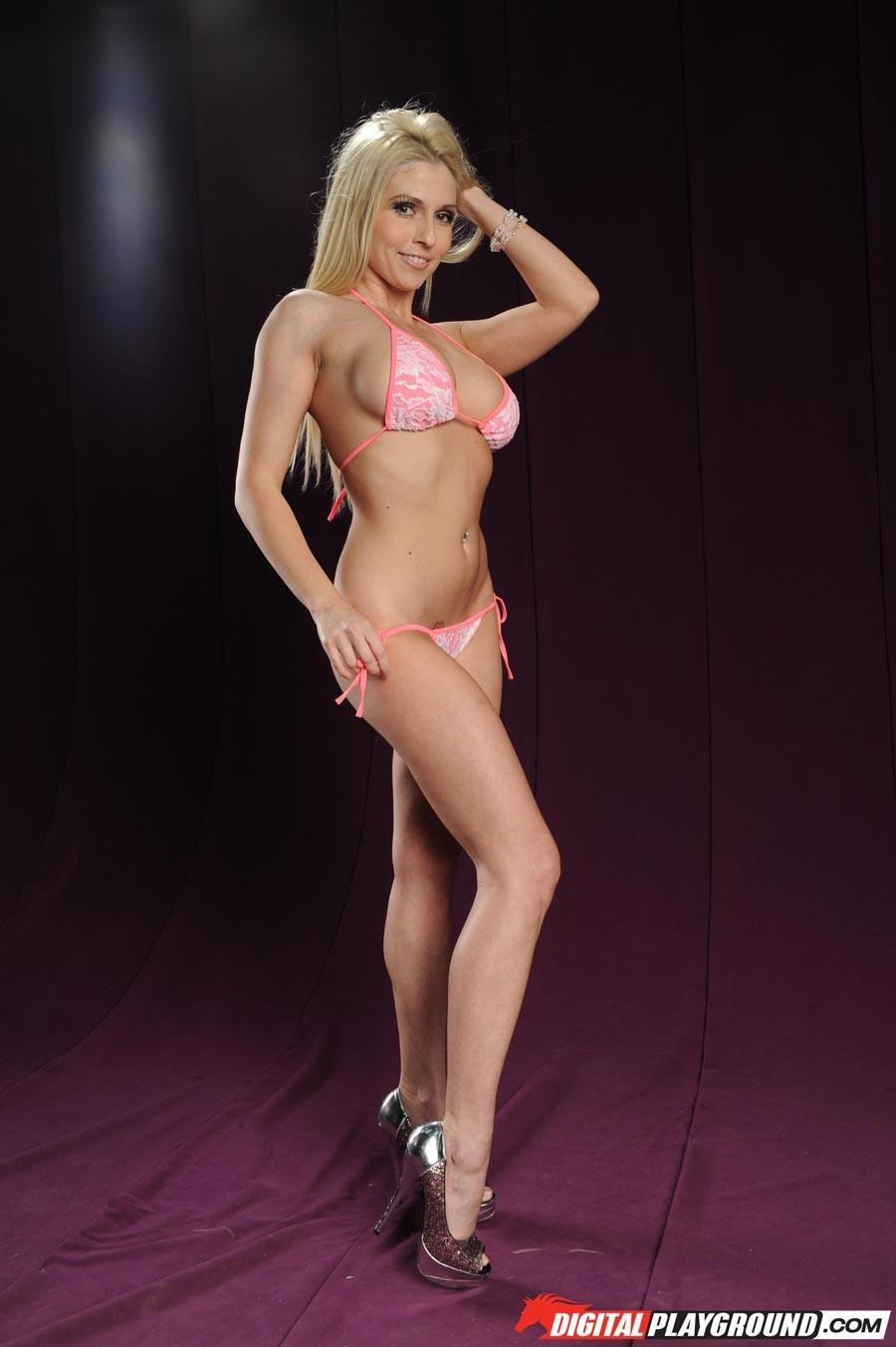 Голая блондинка в розовом купальнике показывает грудь
