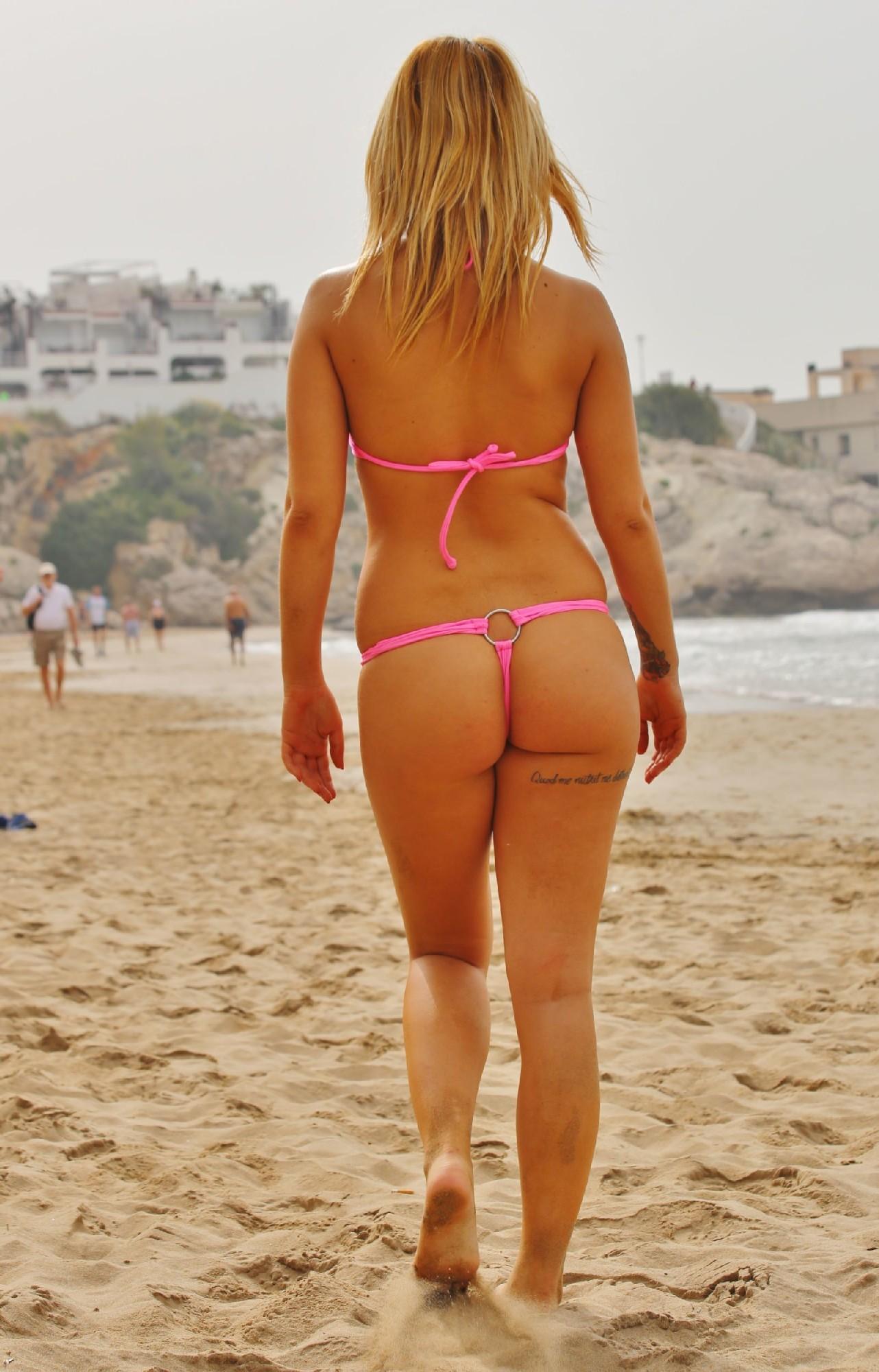 Блондинка на пляже в розовом купальнике раздевается