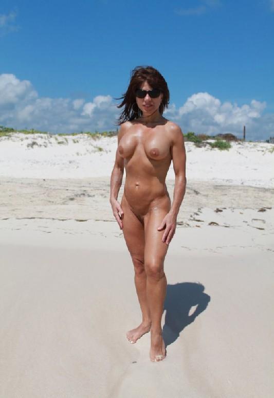 Горячая модель в зрелом возрасте позирует на пляже