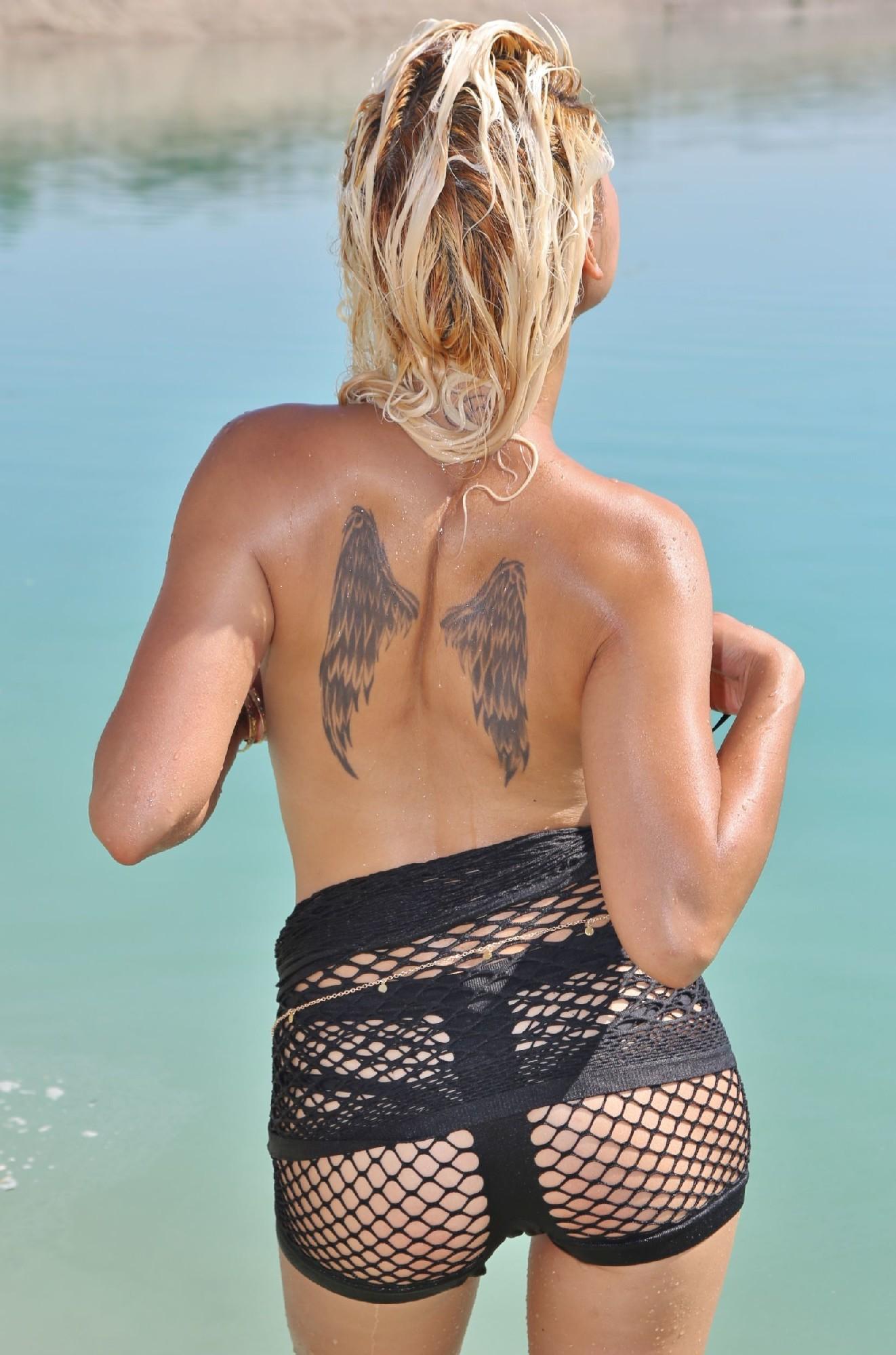 Блонда с татуировкой крыльев на спине, изгибается в разных позах на пляже