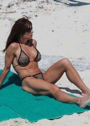 Горячая модель в зрелом возрасте позирует на пляже - фото 2