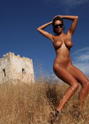 Девушка с большими сиськами фотографируется в поле - фото 32
