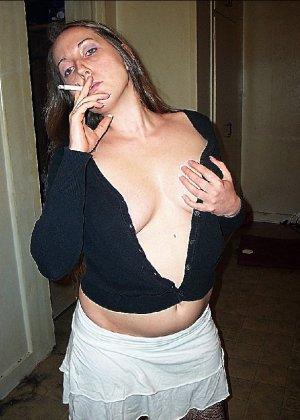 Молодая секси куколка курит сигарету, а потом приспускает штаны и подымает кофту - фото 7