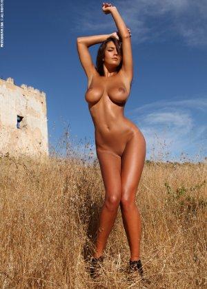Девушка с большими сиськами фотографируется в поле - фото 39