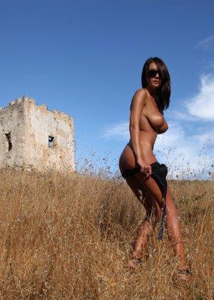 Девушка с большими сиськами фотографируется в поле - фото 16