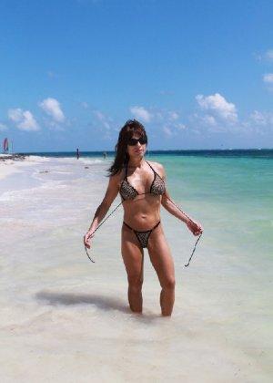 Горячая модель в зрелом возрасте позирует на пляже - фото 1