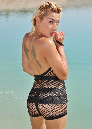 Блонда с татуировкой крыльев на спине, изгибается в разных позах на пляже - фото 8