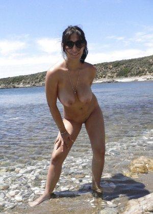 Раскованная брюнетка позирует на пляже и в доме - фото 4