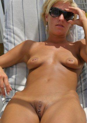 Короткостриженая деваха с пирсингом в письке, откровенно позирует летом - фото 2
