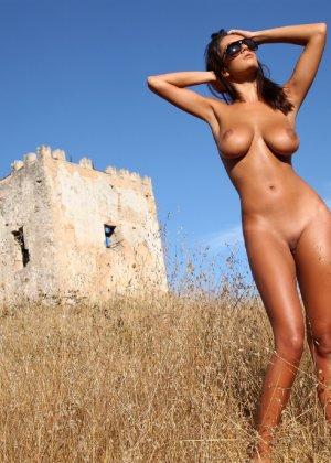 Девушка с большими сиськами фотографируется в поле - фото 22