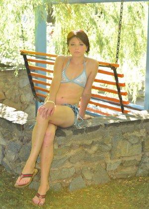 Красивая молодая девчонка в купальнике позирует под деревом - фото 9
