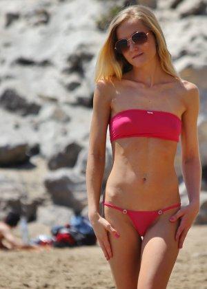 Блондинка в купальнике прогуливается по пляжу и приоткрывает свои сиськи - фото 4