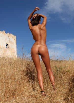Девушка с большими сиськами фотографируется в поле - фото 40