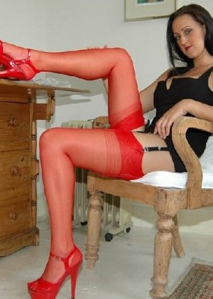 Секси шлюшка позирует в красных чулках перед фотокамерой - фото 1