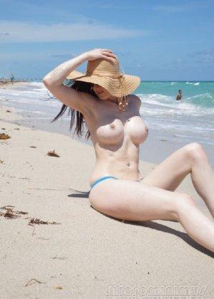 Девка с обворожительной фигурой в купальнике в дырочку лежит на песке - фото 31