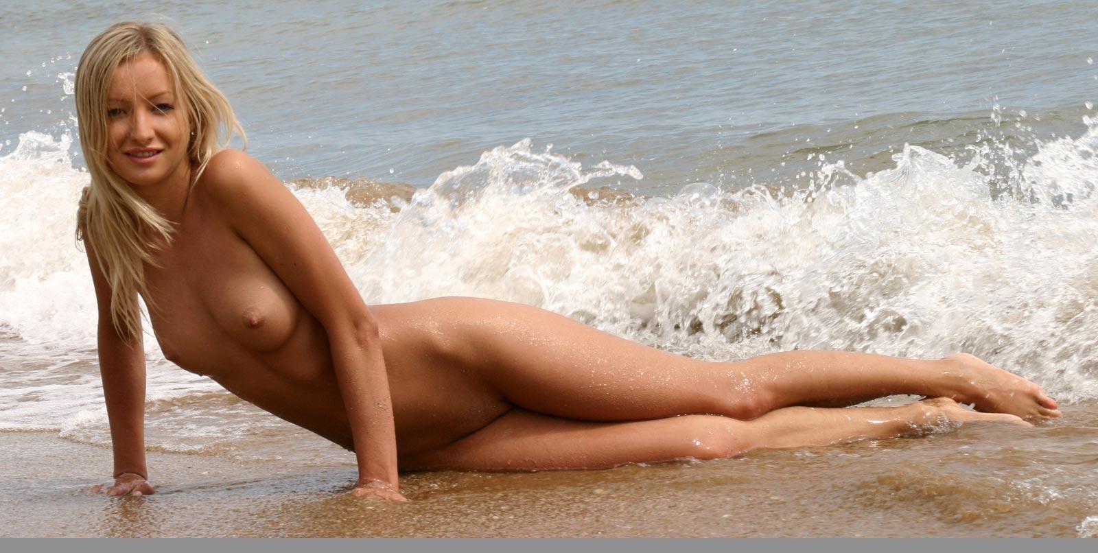 Красивая блондинка показывает стройную фигуру, плескаясь на море и выходя на нежный песок
