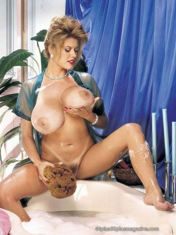 Пухлая зрелая домохозяйка в чулках забирается в ванну, ее одежда мокрая, но ее это не смущает, она играет со своими большими буферами
