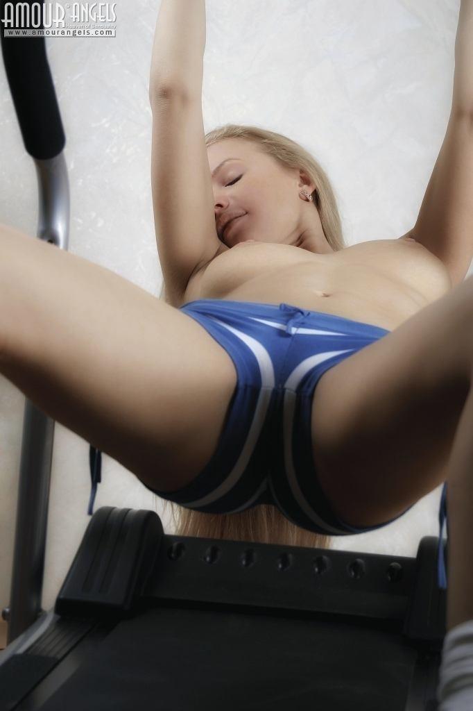 Гибкая блондинка Анна занимается на тренажере голой, как только снимает шорты, так она чувствует себя свободней, тем более что выходит классное эротическое соло