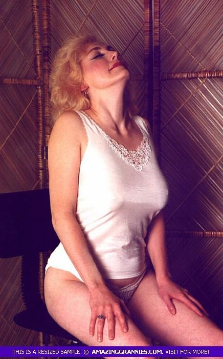 Пожилая грудастая блондинка раздевается до гола, иногда сжимая свои сиськи