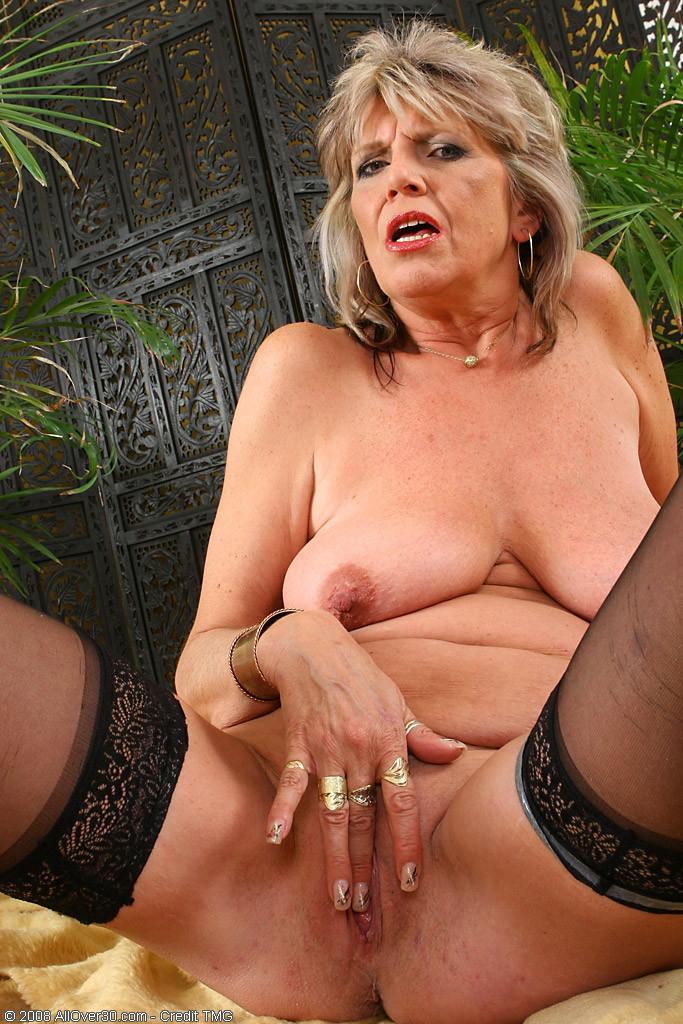 Пожилая женщина не стесняется показывать свое обнаженное тело – она раздевается перед камерой