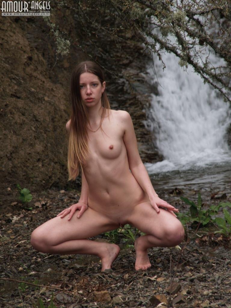 Девушка эротично позирует у водопада