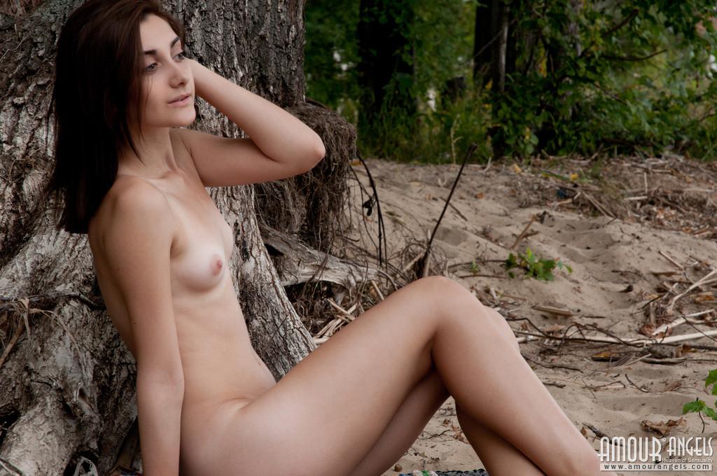 Худая девушка позирует голой в лесу