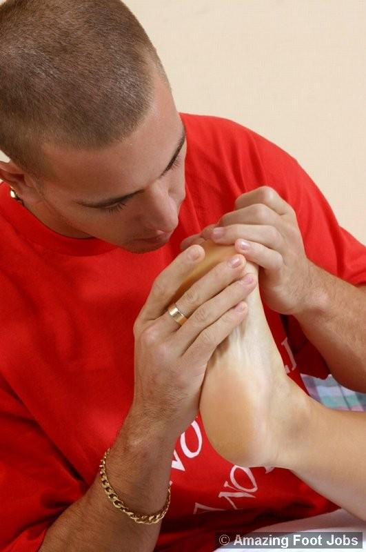 Лысый парень облизывает пальцы ног своей подруге
