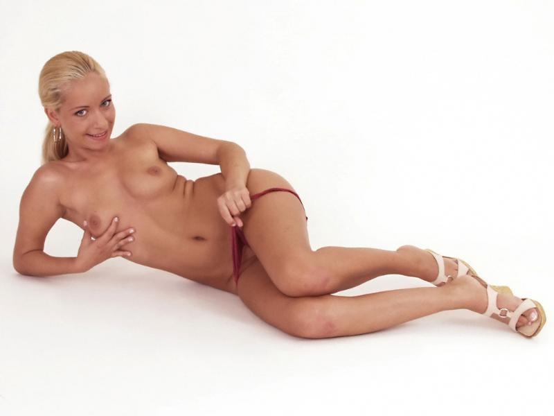 Блондинка эротично приспускает трусики