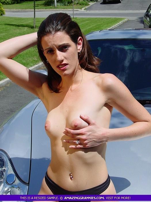Молодая женщина показывает свою маленькую грудь, облокатившись на капот спортивного авто
