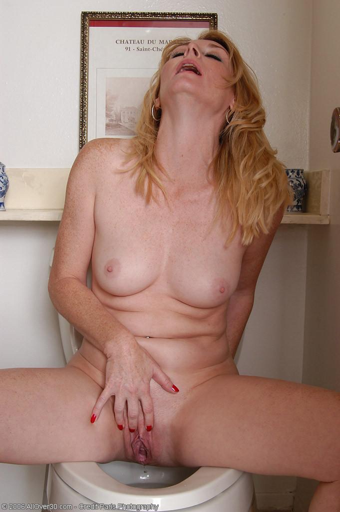 Сексуальная и зрелая блондинка позирует обнаженной на унитазе