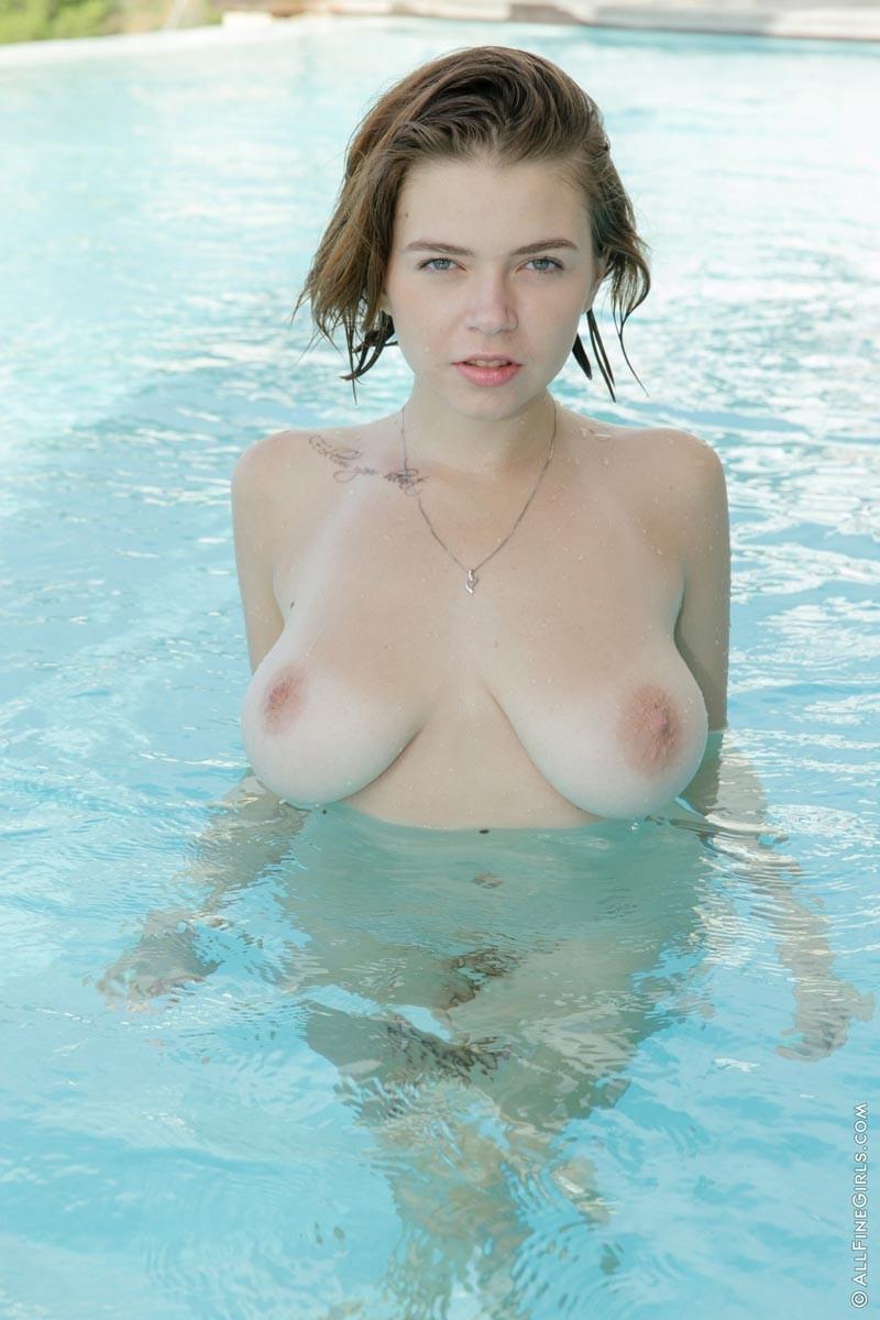 Висячие натуральные сиськи хорошего размера у телки, которая купается в бассейне голой, а между ног у нее бритая пизда