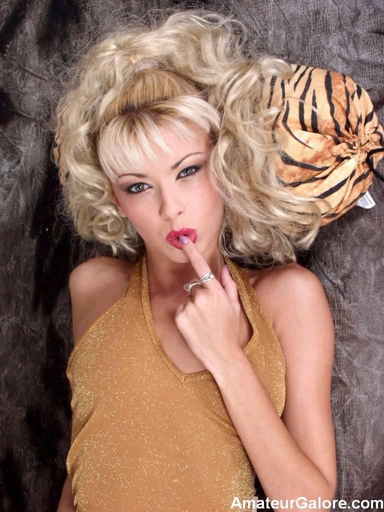 Блондинка с длинными волосами позирует со своей мягкой игрушкой
