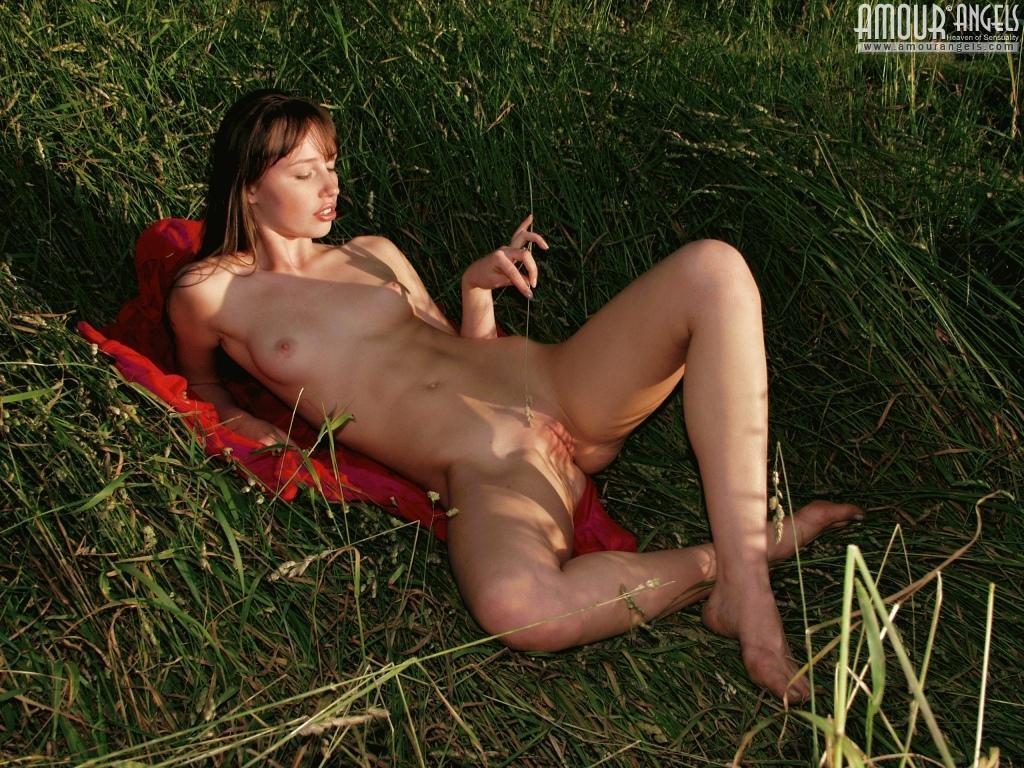 Анжела на отдыхе в деревне играет голой в высокой траве, у нее бритая красивая вагина и небольшие титьки