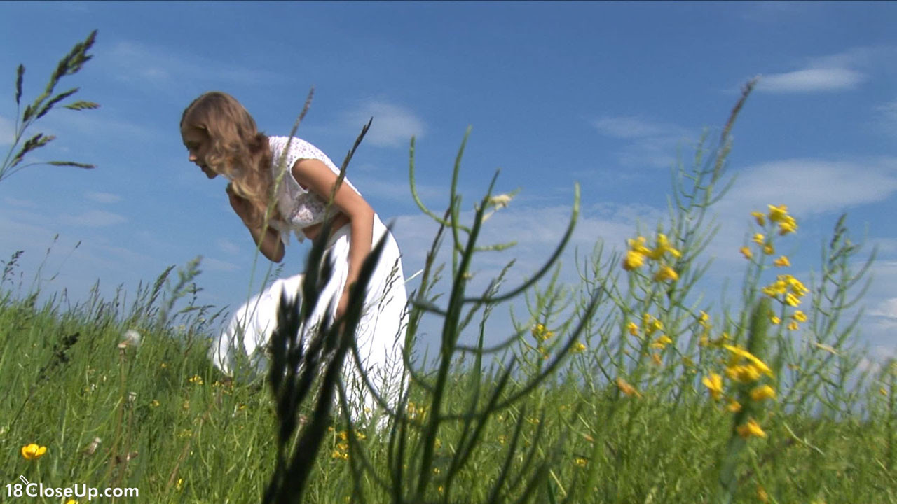 Кристина на свежем воздухе и в высокой траве показывает бритую вагину и узкую анальную дырку крупным планом