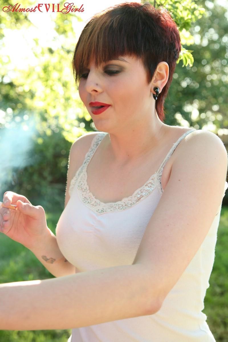Морна вышла покурить, но пока она курит, еще и показывает сиськи и спускает трусы, демонстрируя пизду на улице