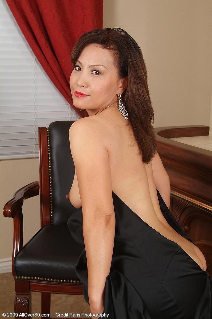 Зрелая азиатка элегантно приподнимает платье и показывает себя